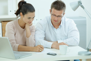 "Happy young casual couple sitting at desk working together at home office, smiling. Click here for more ""People at Home"" images: [url=my_lightbox_contents.php?lightboxID=1507925]<img class=""img-responsive img-"" alt="""" src="""" />[/url]"