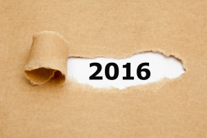 Year 2016 appearing behind torn brown paper.